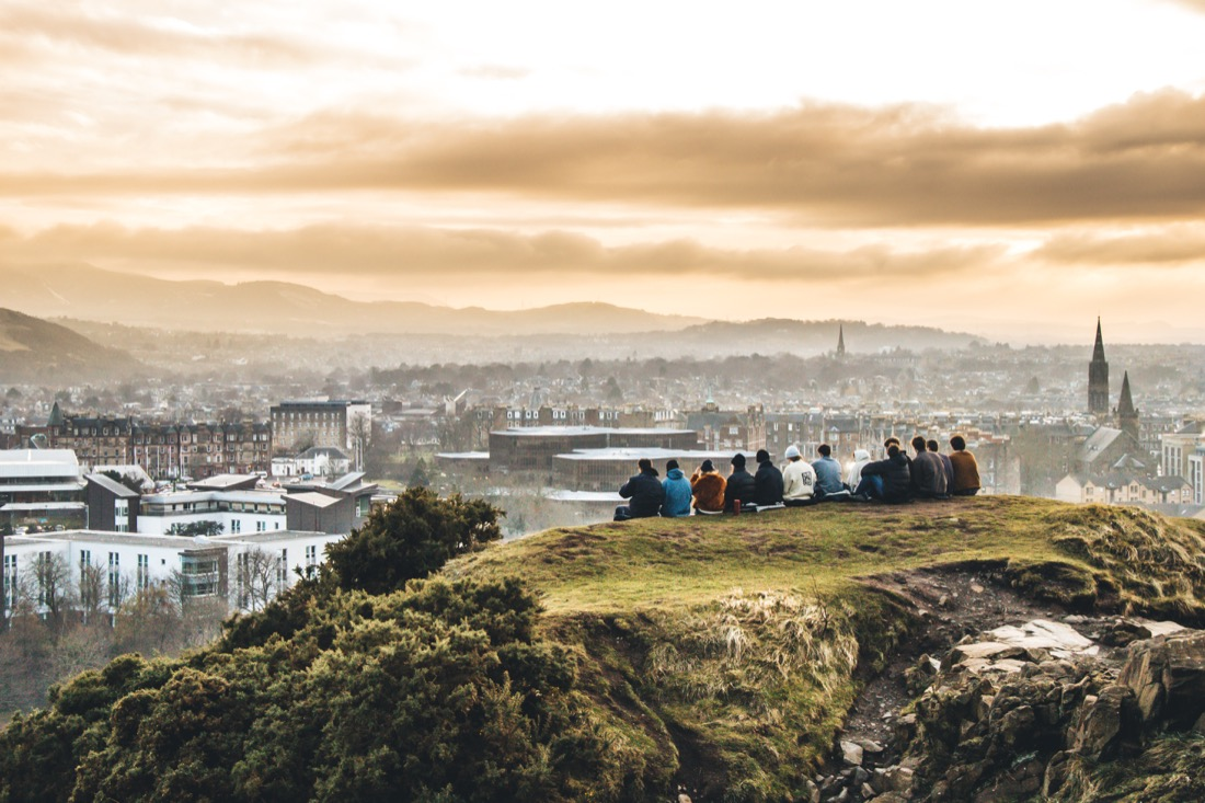 Group of students overlook Edinburgh at sunset from Arthur's Seat. with orange tones