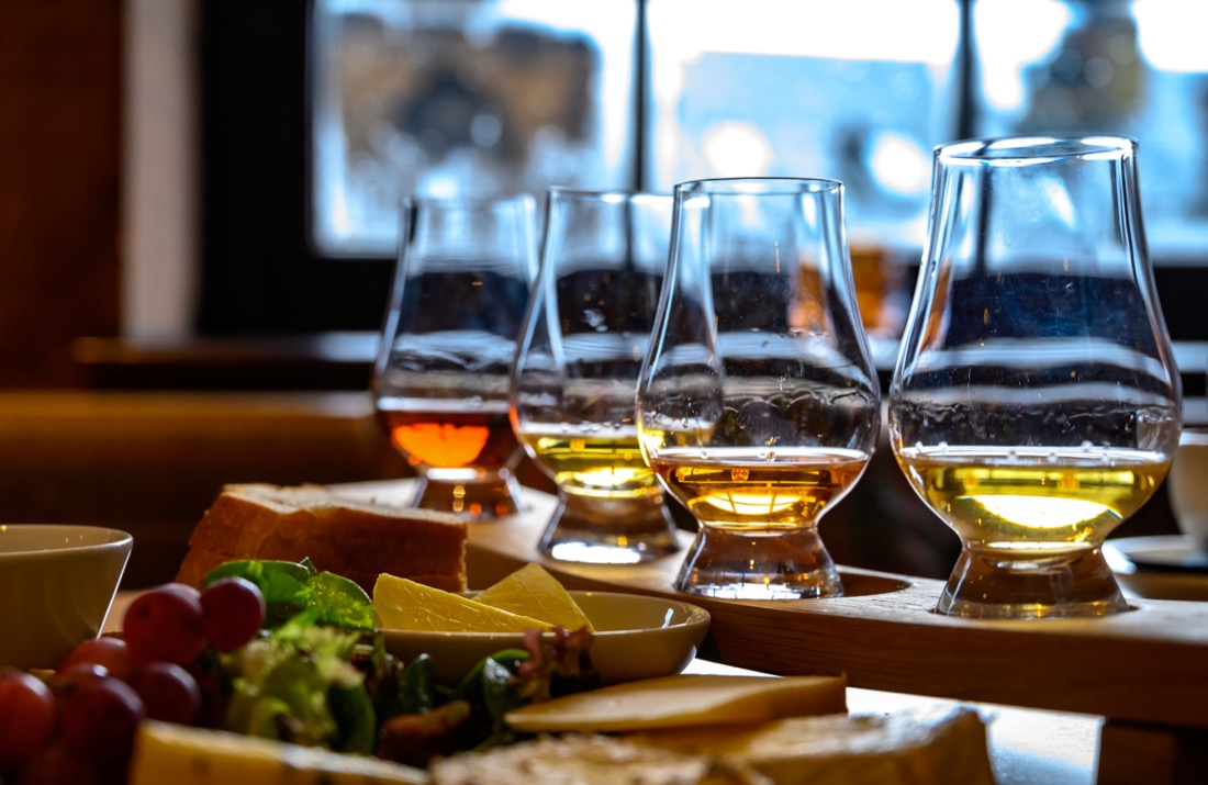 Whisky, plate with Scottish cheeses and variety of Scotch in glasses in Edinburgh food
