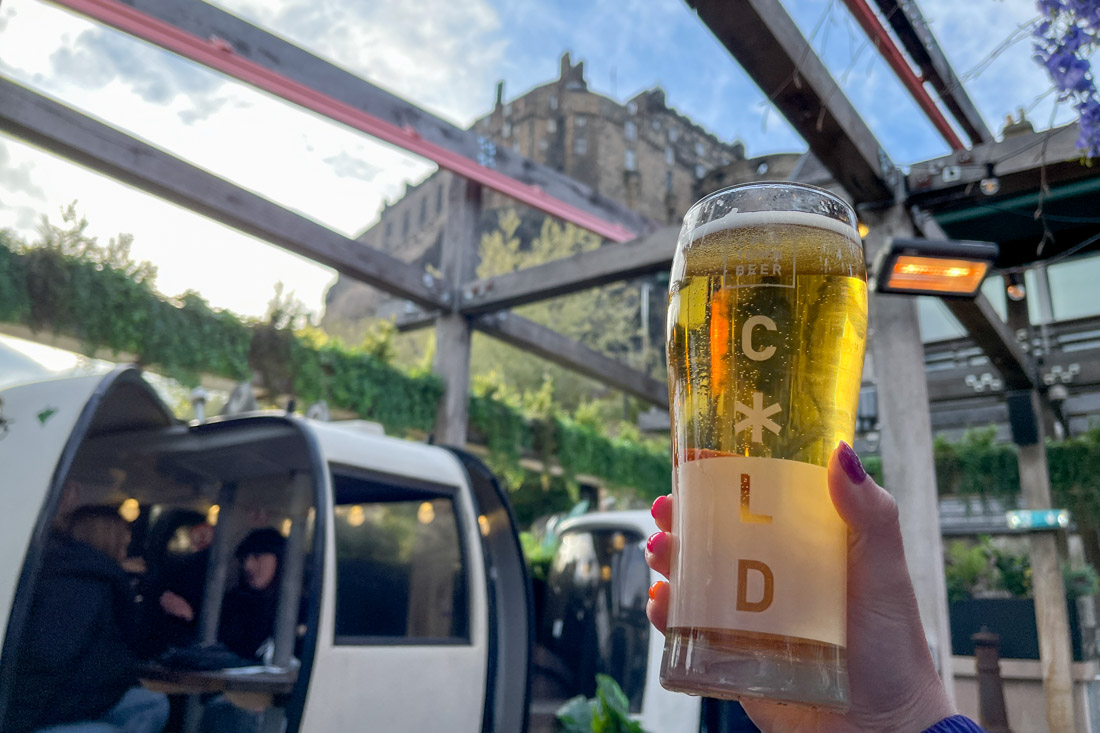 Hand holding pint on rooftop with Edinburgh Castle views from Cold Town House Edinburgh
