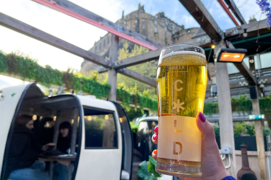 Hand holding a pint of beer with Edinburgh Castle views at Cold Town House