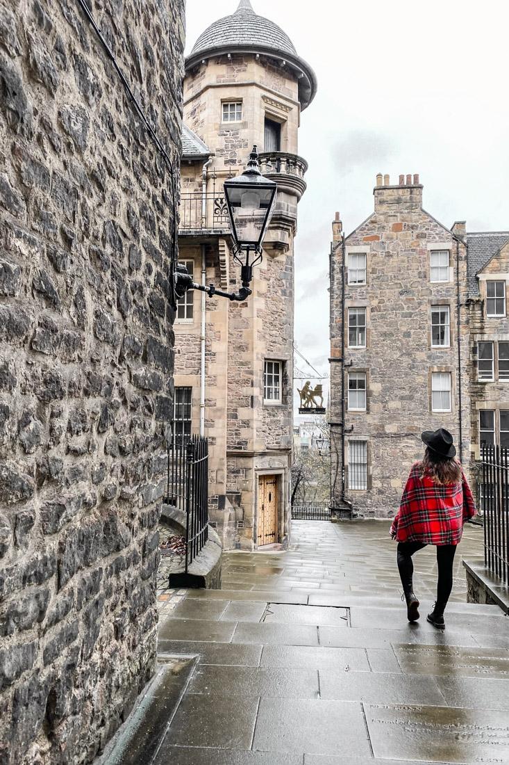 Woman wearing tartan cape at Writers Museum Makars Court Gemma Old Town in Edinburgh_